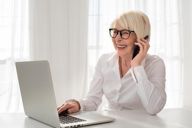 Smiley vieille femme parlant au téléphone Photo gratuit