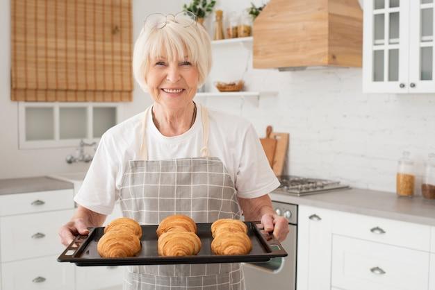 Smiley vieille femme tenant un plateau avec des croissants Photo gratuit