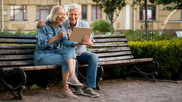 Smiley Vieux Couple à L'extérieur Avec Tablette Photo Premium