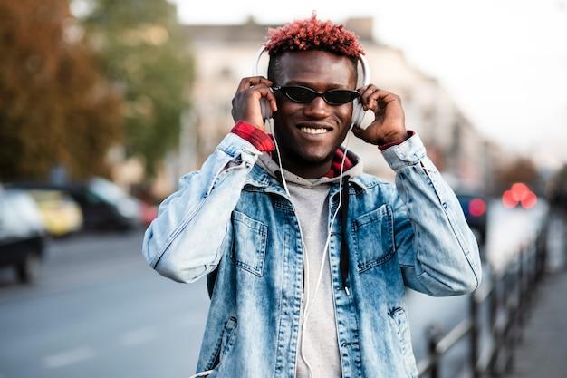 Smiley vue de face jeune homme dans la ville Photo gratuit
