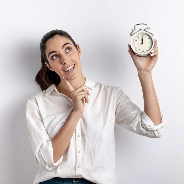 Smiley Woman Holding Clock Photo gratuit
