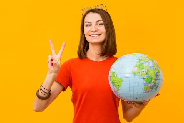 Smiley Woman Holding Globe Et Faire Signe De Paix Photo gratuit