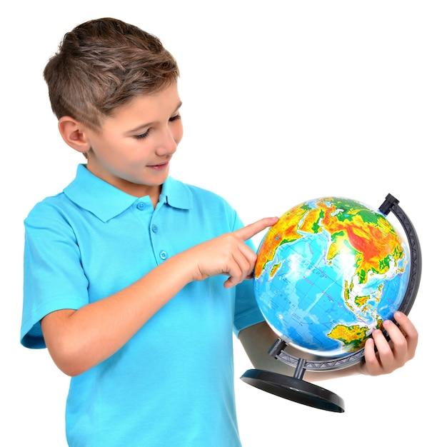 Smiling Boy In Casual Holding Globe Avec Dans Les Mains Et Les Points Dessus Isolé Sur Blanc Photo gratuit