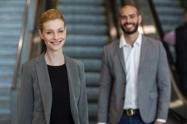 Smiling Businesspeople Avec Bagages Debout Devant Un Escalator Photo gratuit