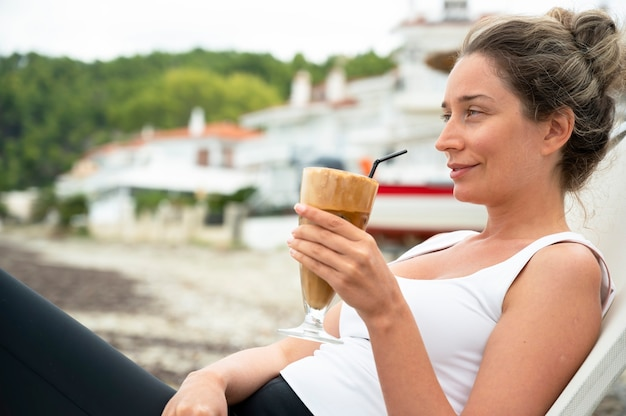 Smiling Caucasian Woman Holding Café Sur Une Plage Avec De La Mousse Et De La Paille Avec La Ville Photo gratuit