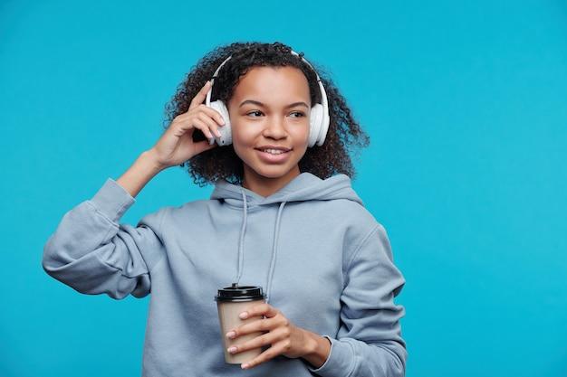 Smiling Teenage Black Pensive écouter De La Musique Dans Des écouteurs Sans Fil Et Boire Du Café Sur Fond Bleu Photo Premium