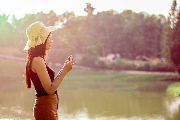 Smilling femme asiatique avec lumière du coucher du soleil Photo Premium