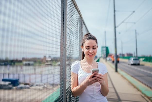 Smling fille se penchant sur une grille. écouter de la musique et utiliser un téléphone debout sur un trottoir. Photo Premium