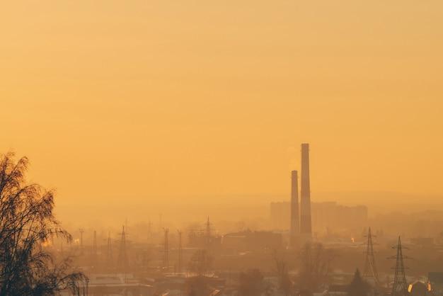 Smog parmi les silhouettes des bâtiments au lever du soleil. Photo Premium