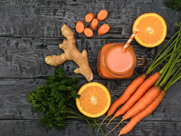 Smoothie aux carottes fraîchement préparé, bouquet de carottes, persil, orange et racine de gingembre sur une table rustique. Photo Premium
