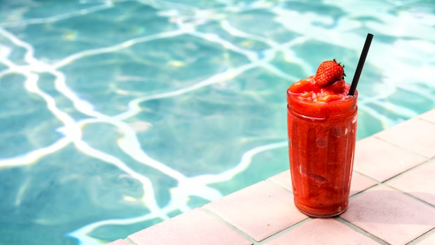 Smoothie aux fraises au bord de la piscine Photo gratuit