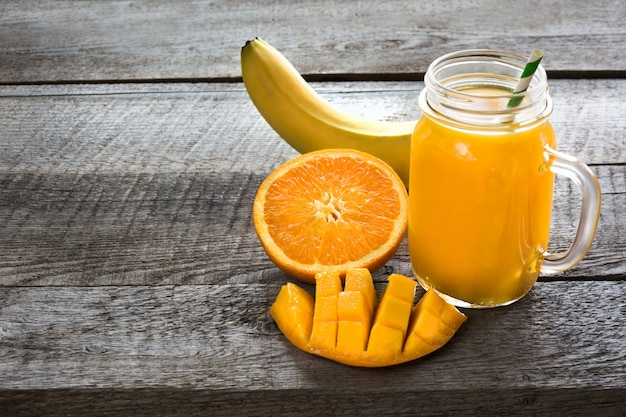 Smoothie aux fruits tropicaux: mangue, banane, orange dans un bocal en verre sur le fond en bois. Photo Premium