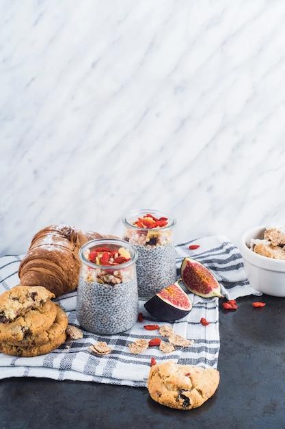 Smoothie en bonne santé avec des biscuits au dos et un croissant sur une serviette sur un fond texturé en marbre Photo gratuit