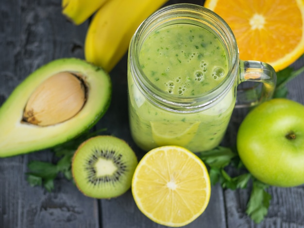 Un Smoothie Fraîchement Préparé D'avocat, De Banane, D'orange, De Citron Et De Kiwi Sur Une Table En Bois. Régime Alimentaire Végétarien. Photo Premium