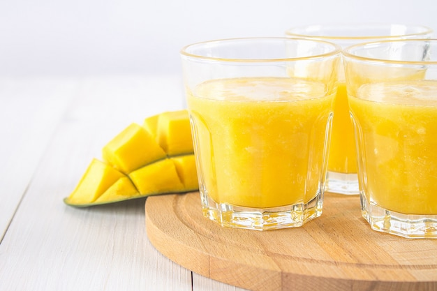 Smoothie jaune de mangue, banane et orange sur une table en bois blanche. Photo Premium