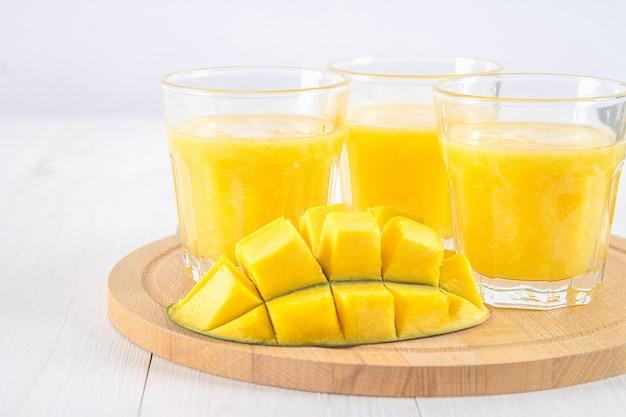 Smoothie jaune de mangue, banane et orange sur une table en bois blanche. Photo Premium