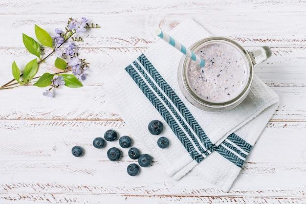 Smoothie plat aux bleuets à côté de la fleur Photo gratuit