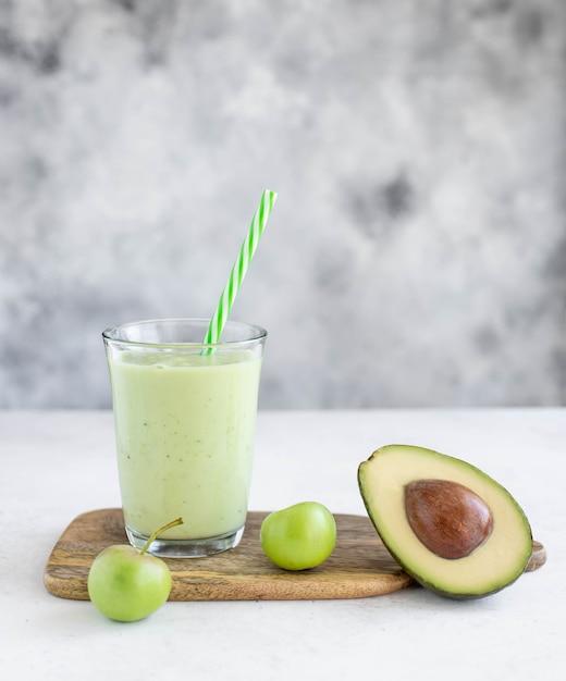 Smoothie santé à la pomme avocat-concombre dans un verre avec une paille Photo Premium