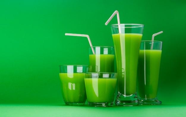 Smoothie vert bio, jus de pomme sur isolé sur fond vert avec espace copie, cocktail de céleri frais Photo Premium