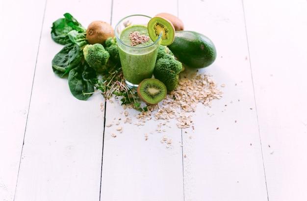 Smoothie Vert Frais Et Savoureux Avec Des Ingrédients Sur Une Surface En Bois Photo Premium