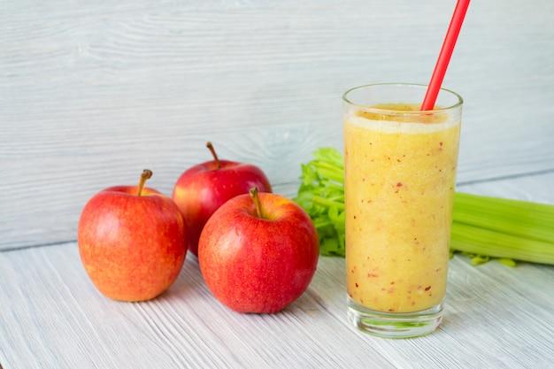 Smoothies aux pommes et céleri dans un verre avec une paille sur une table Photo Premium