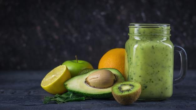 Smoothies D'avocats, Bananes, Kiwis Et Herbes Sur Une Table Noire En Bois Noire. Régime Alimentaire Végétarien. Photo Premium