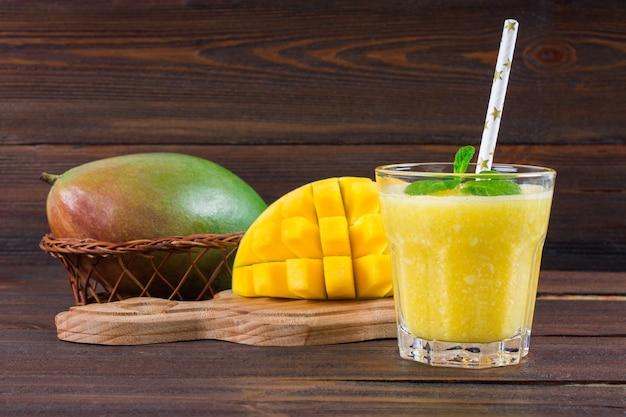 Smoothies mangue avec paille et menthe dans un bécher en verre. assiette à la mangue en tranches. Photo Premium