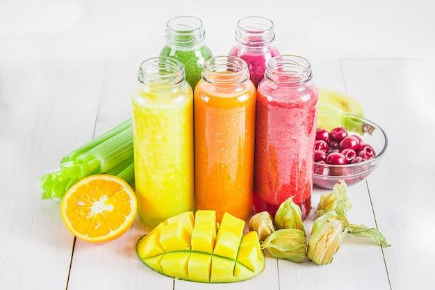 Smoothies multicolores dans des bouteilles de mangue, orange, banane, céleri, baies, sur une table en bois. Photo Premium