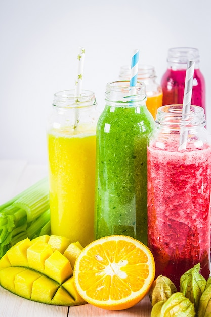 Smoothies multicolores dans des bouteilles de mangue, orange, banane, céleri, baies, sur une table en bois. Photo Premium