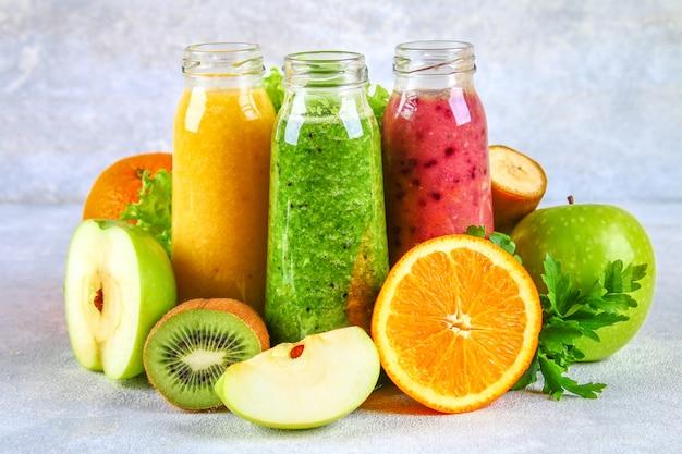 Smoothies verts, jaunes et violets dans des bouteilles de groseilles, persil, pomme, kiwi, orange sur une table grise. Photo Premium