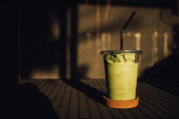 Smoothy lait de thé vert dans un verre en plastique. Photo Premium