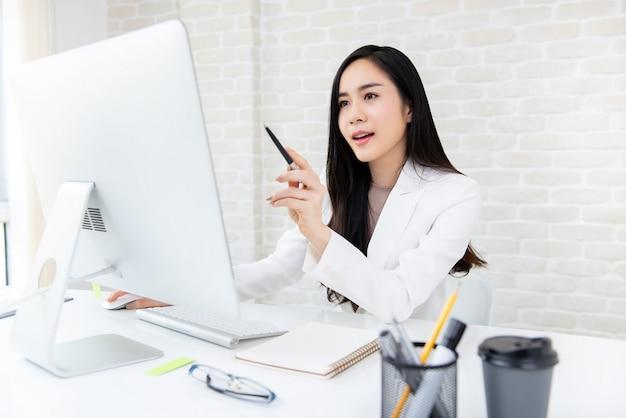 Smsart belle femme asiatique travaillant sur ordinateur au bureau Photo Premium