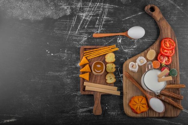 Snack Board Avec Des Craquelins Et Des Légumes Isolés Sur Fond Noir Photo gratuit