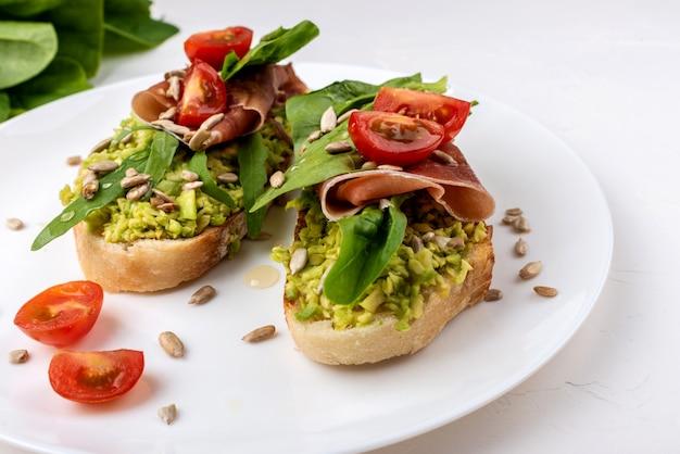 Snacks Sandwichs Avec Jambon, Avocat, Tomates Et Salade De Feuilles. Photo Premium