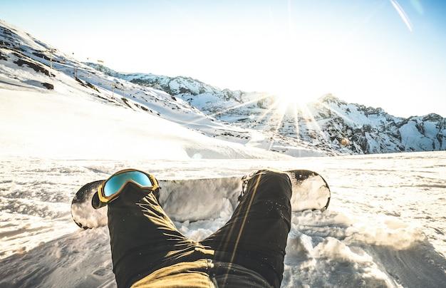Snowboarder Assis Au Coucher Du Soleil Sur Un Moment De Détente Dans La Station De Ski Des Alpes Européennes Photo Premium