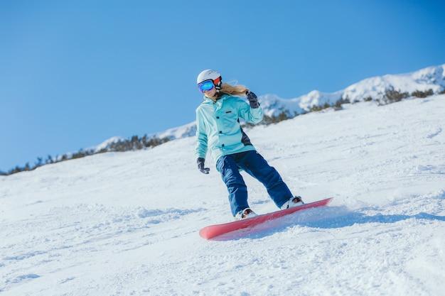 Snowboarder sur les pistes un matin ensoleillé. fille en habits de snowboarder. Photo Premium