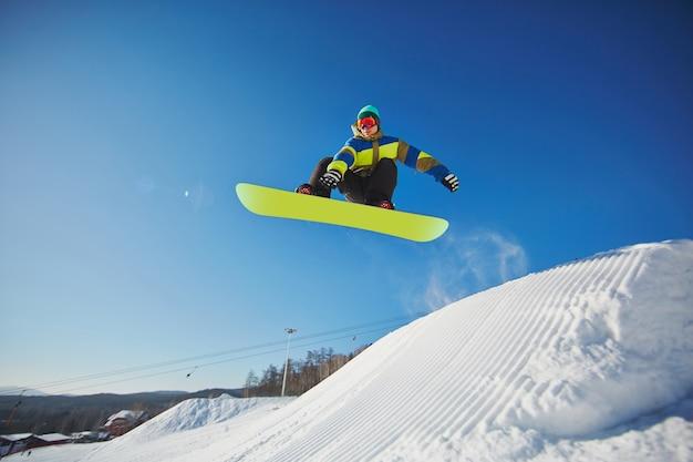 Snowboarder sautant à travers le ciel bleu Photo gratuit