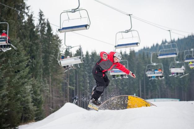 Snowboarder voler d'un obstacle en jour d'hiver Photo Premium