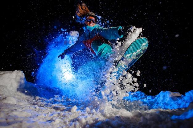 Une Snowboardeuse Vêtue D'un Vêtement De Sport Orange Et Bleu Effectue Des Tours Sur La Neige Photo Premium