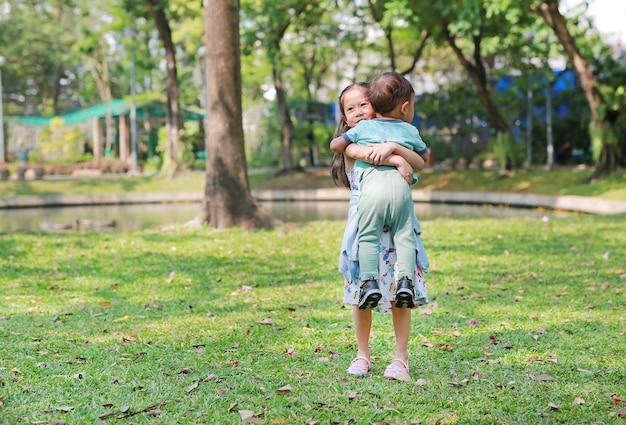 Soeur asiatique portant son petit frère dans le jardin en plein air. Photo Premium