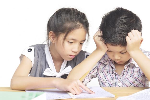 Une soeur essaie d'apprendre à son petit frère coquin à faire ses devoirs Photo gratuit