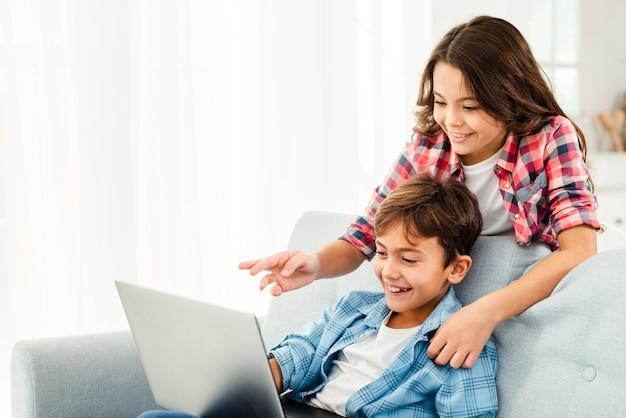 Sœur, montrer, frère, quelque chose, sur, ordinateur portable Photo gratuit