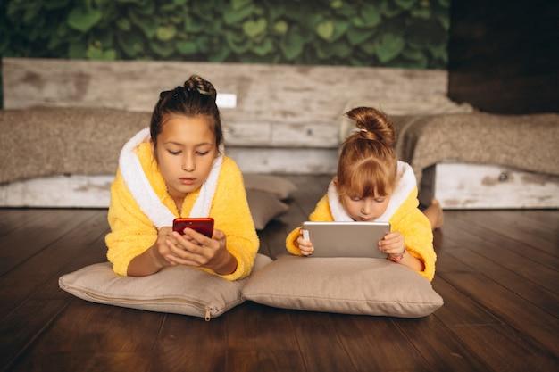 Soeurs gisant sur le sol avec téléphone et tablette Photo gratuit