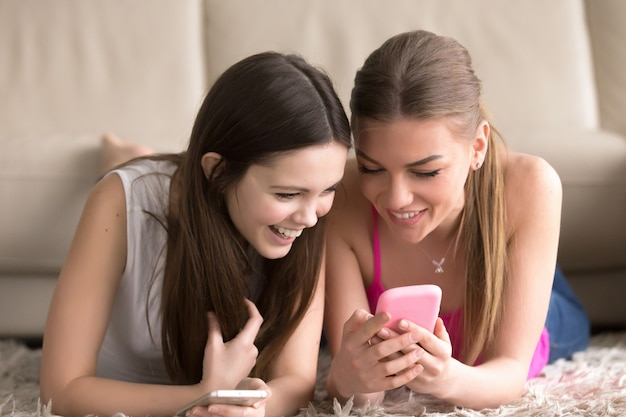 Sœurs partageant des photos amusantes sur téléphone portable Photo gratuit