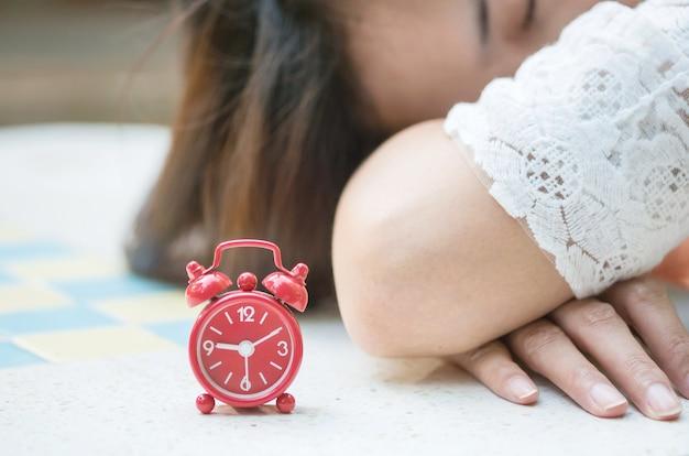 Soft focus de closeup réveil rouge avec une femme endormie floue sur fond de bureau en marbre Photo Premium
