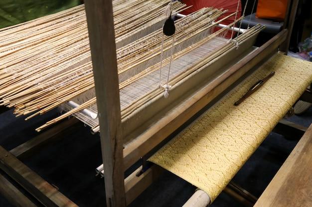 Soie dorée sur métier à tisser, coton sur métier à tisser manuel en asie Photo Premium