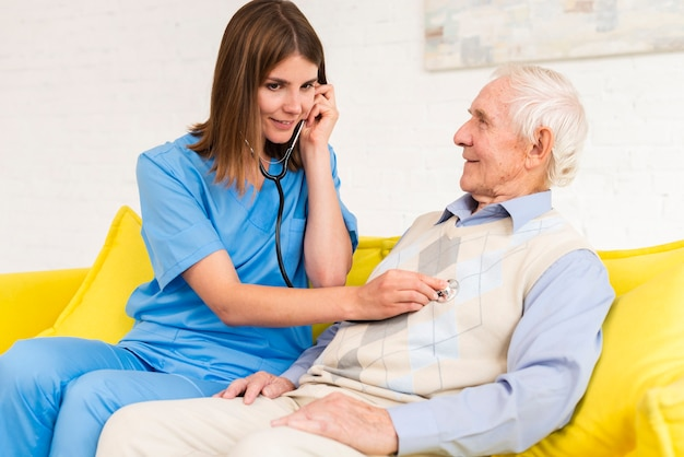 Soignant à l'aide d'un stéthoscope sur le vieil homme Photo gratuit