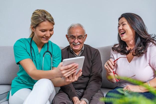 Un soignant à domicile et un couple de personnes âgées Photo Premium