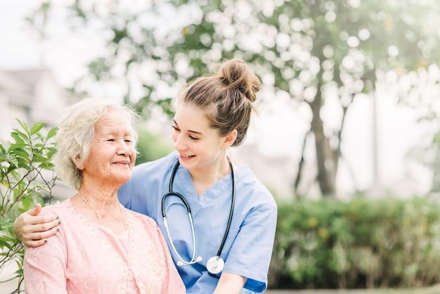 Soignant avec une femme âgée asiatique en plein air Photo Premium