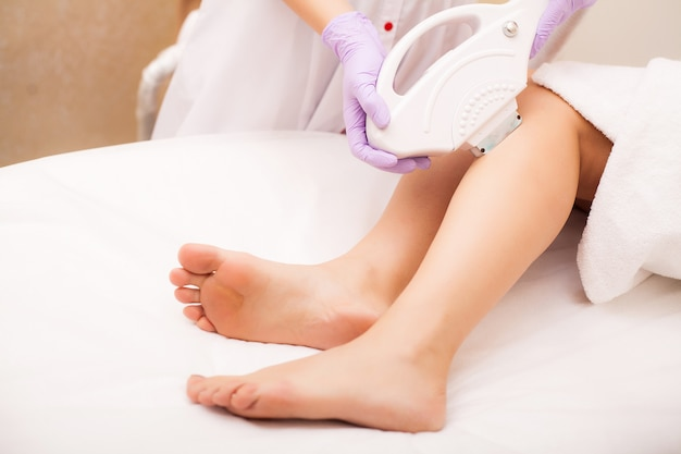 Soin de la peau. épilation sur les jambes, procédure au laser à la clinique. Photo Premium